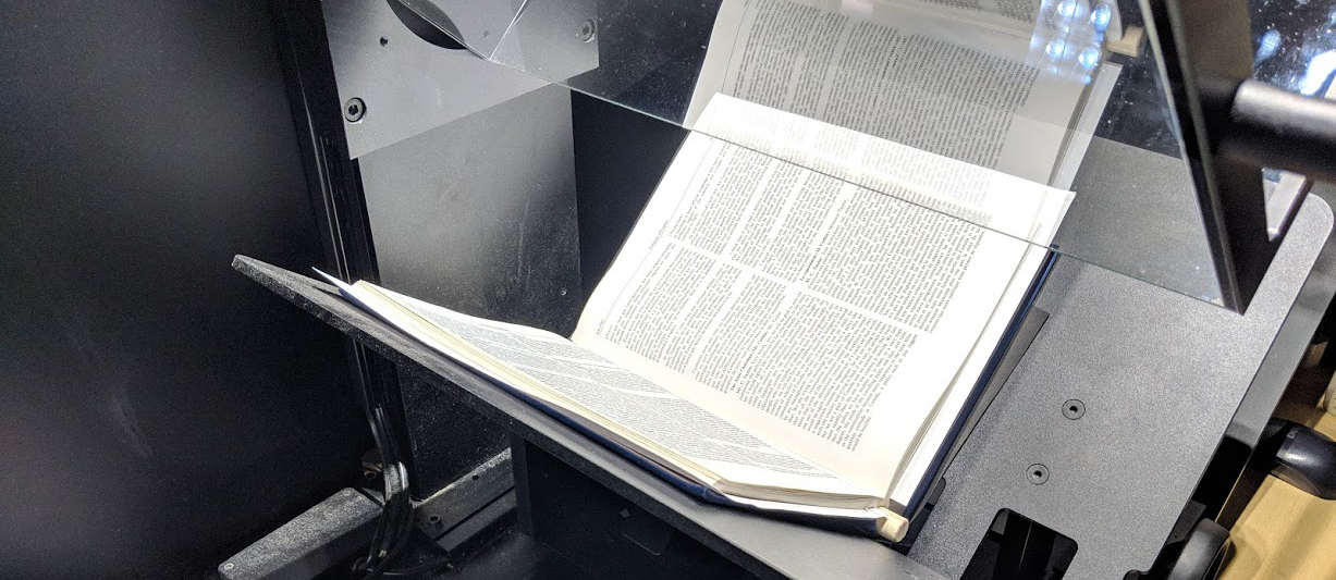 An open book sits inside a digital scanner.